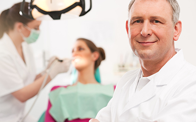 Dentist with patient and staff in backgorund