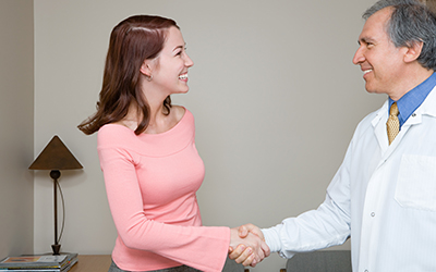 Woman shaking dentists hand