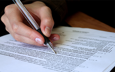 A hand holding a pen writing on paperwork