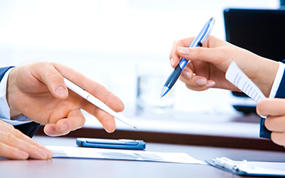 A close-up of two people's hands working on paperwork