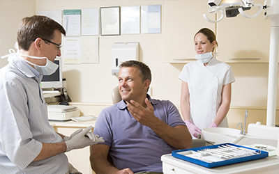 A dentist and dental assistant talking with a male patient.